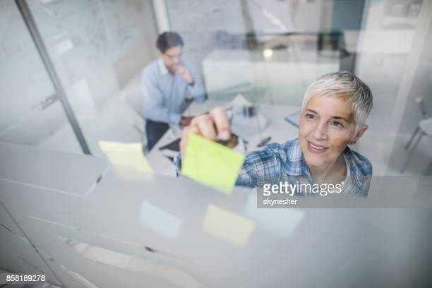 Above view of mature businesswoman writing on adhesive notes on the glass.
