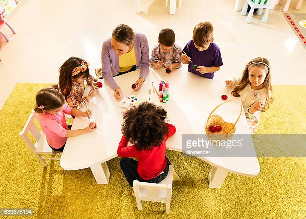 Above view of preschool teacher and children coloring Easter eggs.