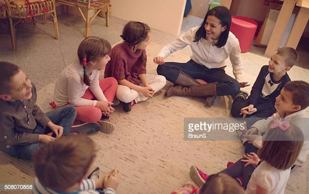 Vista de arriba de preescolar maestro hablar con Grupo de los niños.