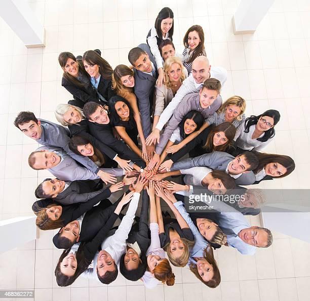 上から見る笑顔が集まるビジネスの人々の手で統一しております。