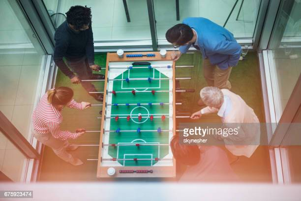 Above view of start up team playing table soccer on a break.