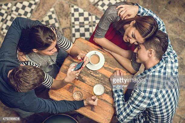 Above view of two young couples enjoying in a cafe.