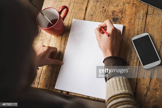 Vue plongeante de Personne non reconnaissable par écrit sur papier. Espace texte