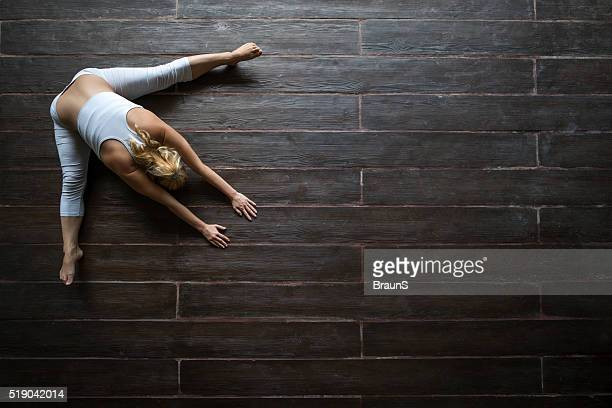Above view of woman doing relaxation exercises on wooden floor.