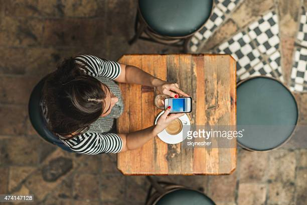 Above view of young woman text messaging in a cafe.