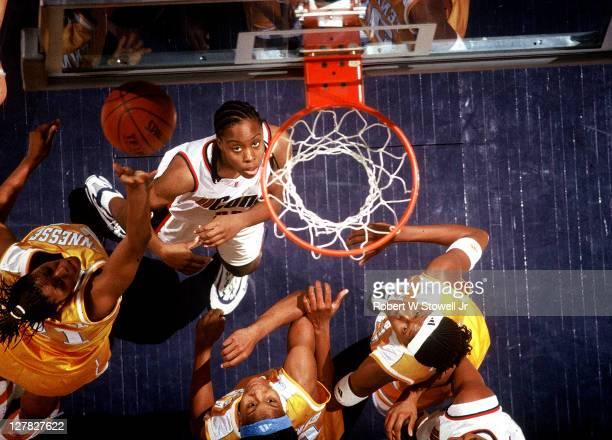 Abovethenet view of American basketball player Kenitra Johnson of the University of Connecticut as she is surrounded by players from the University...