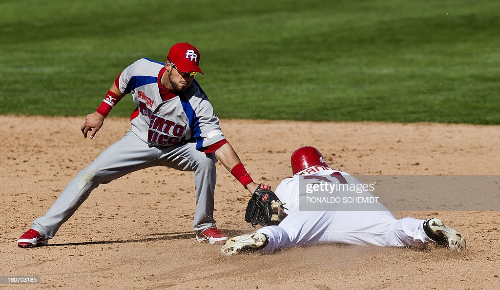 Abraham Almonte (R) of Leones del Escogido of Dominican Republic slides safe in second base in a match against Criollos de Caguas of Puerto Rico during the 2013 Caribbean baseball series, on February 4, 2013, in Hermosillo, Sonora State, in the northern of Mexico. AFP PHOTO/Ronaldo Schemidt