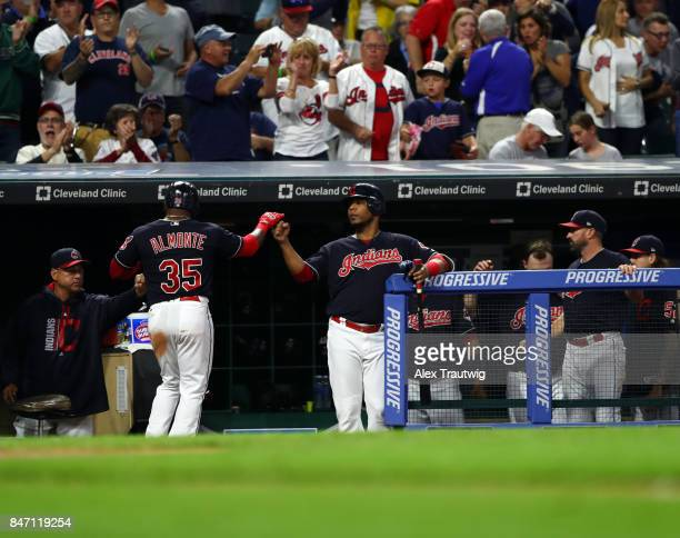 Abraham Almonte of the Cleveland Indians celebrates with Edwin Encarnacion after scoring in the bottom of the third inning of the game against the...