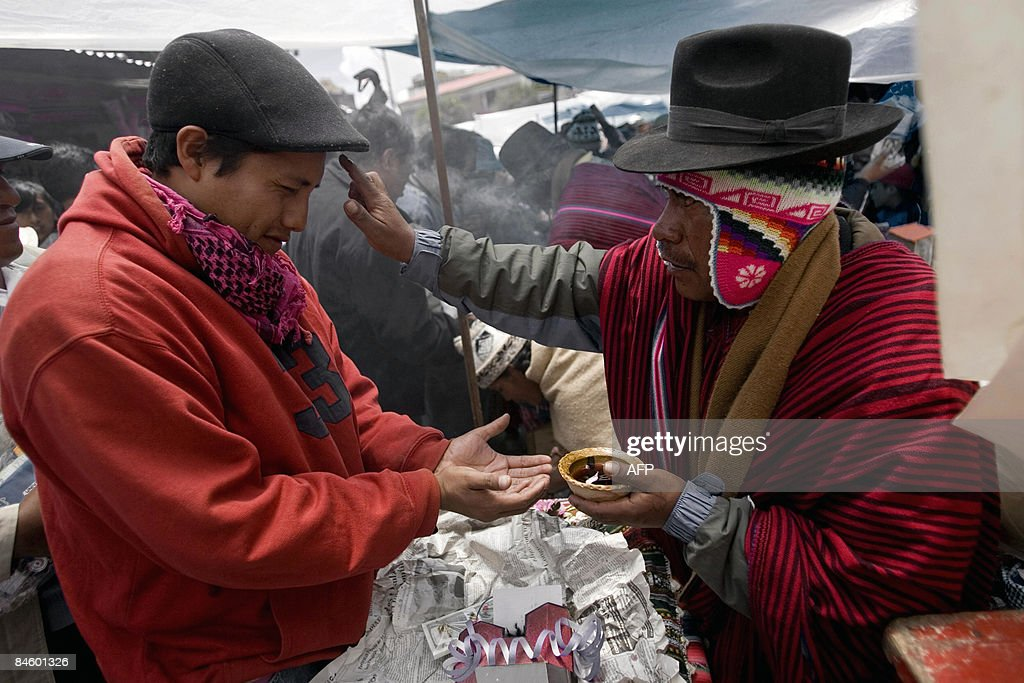 Abraham Bojorquez, leader of the rap group Ukamaku y Ke ('That's it, so what?' in Aymara language), is blessed by a witch doctor on a traditional ritual at El Alto, an impoverished satellite city overlooking La Paz, on January 24, 2009. Despite widespread harsh feelings towards US policies, Bolivian youths embrace US Hip-Hop culture as a way to vent their anger over historical oppression and exploitation. Through songs that praise President Evo Morales' 'democratic revolution' and a claim for social changes, Bolivian rappers believe there is no contradiction between their 'gringo' look and the anti-imperialist slant. Largely descendants of Aymara indigenous migrants from the high plains to the cities of El Alto and La Paz, those youngsters see in the thriving hip-hop scene a chance to voice their plight and channel their young rebellious spirit. AFP PHOTO/Joao Padua MORE