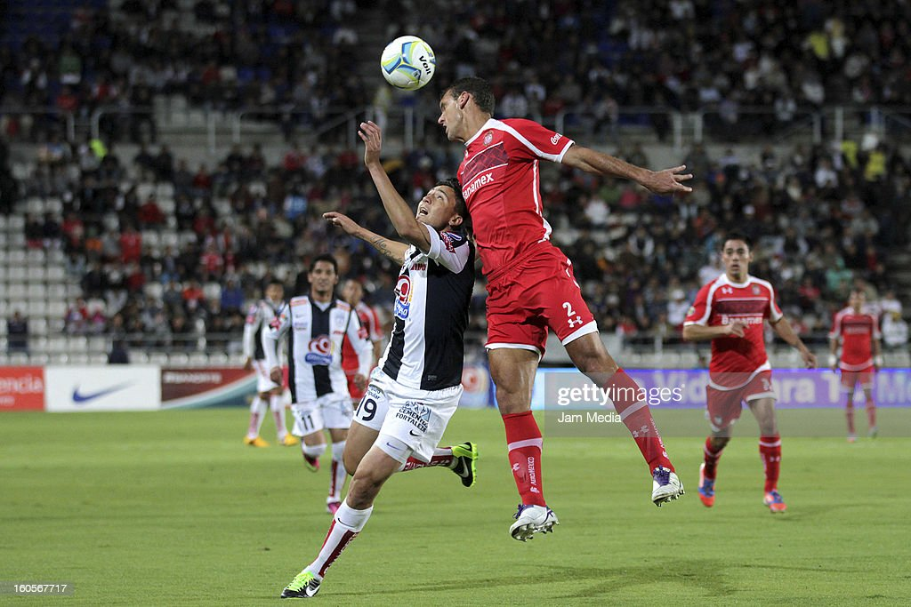 Abraham Dario Carreno (L) of Pachuca struggles for the ball with Diego Novaretti (R) of Toluca during the Clausura 2013 Liga MX at Hidalgo Stadium on february 2, 2013 in Pachuca, Mexico.