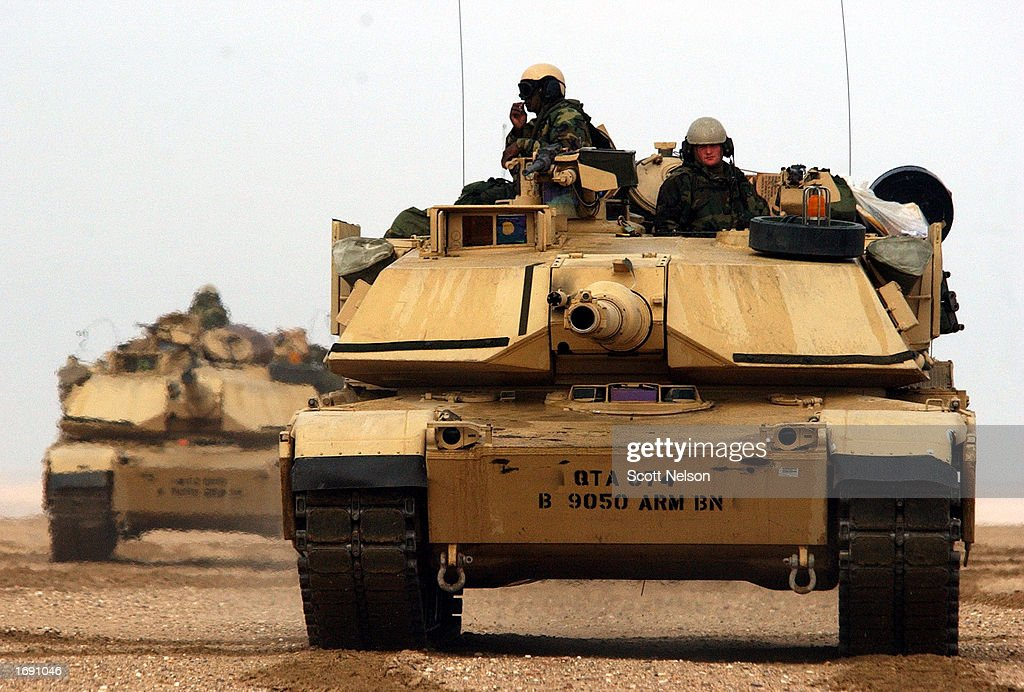 Abrams tanks from the Charlie company 464 Armored Battalion depart for task force manuevers December 17 2002 near the Iraqi border in the Kuwaiti...