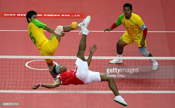 Abrian Sihab of Indonesia competes with Alung Ko Oo of Burma while Thant Zin Oo looks on during the Men's Team Double Final of the Sepak Takraw...