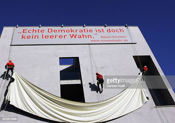 Abseilers unveil a banner carrying the Albert Einstein quote 'genuine democracy is nevertheless no empty illusion' on the external wall of the Swiss...