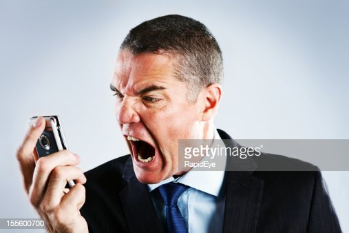 Absolutely furious businessman shouts into cell phone