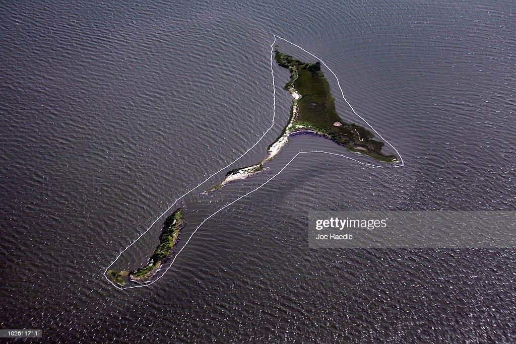 Absorbent material is seen ringing an island as efforts are made to keep the oil from the Deepwater Horizon spill off the land on July 3, 2010 near Grand Isle, Louisiana. Millions of gallons of oil have spilled into the Gulf since the April 20 explosion on the drilling platform.
