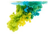 Yellow and green paint dissolving into water, abstract background