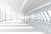 Empty space with rows of white columns forming a long corridor with sunlight illuminating the wide architectural space, casting shadows and a light pattern on the floor. White glossy material reflecti