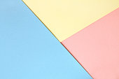 Abstract asymmetrical geometric watercolor paper background in three colors soft pastel pink, blue and yellow trend colors.