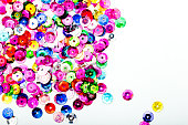 Abstract Background - close up of shiny multi colored round sequins on white background