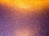 Abstract background filled with shiny gold and purple glitter