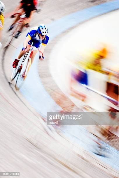 Abstract blur of professional cyclists speeding around a velodrome curve