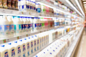 Abstract blur supermarket grocery store refrigerator shelves with fresh milk bottles and dairy products