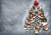 Abstract christmas tree made from cutlery on a dark slate,grey stone or concrete background.Top view with copy space.