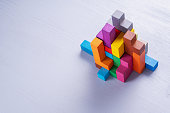 Abstract construction from wooden blocks shapes with copy space. The concept of logical thinking, geometric shapes. Colorful wooden building blocks