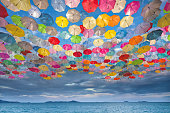 Abstract design of umbrellas flying over sea in the sky