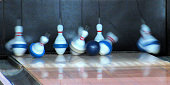 Abstract...This long, horizontal image, shows the moment of impact, of a bowling ball against pins in a bowling lane. This is not a crisp image but is interesting for it's blurred motion of the flying