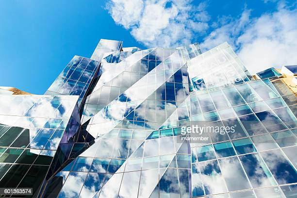 Abstract glass building with sky and clouds reflection, copy space