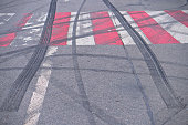 Abstract of Black tire wheels caused by Drift car on the road. Braking at a pedestrian crossing and a road with markings. Stock photo for design