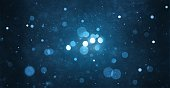 abstract particle bokeh with dark blue background