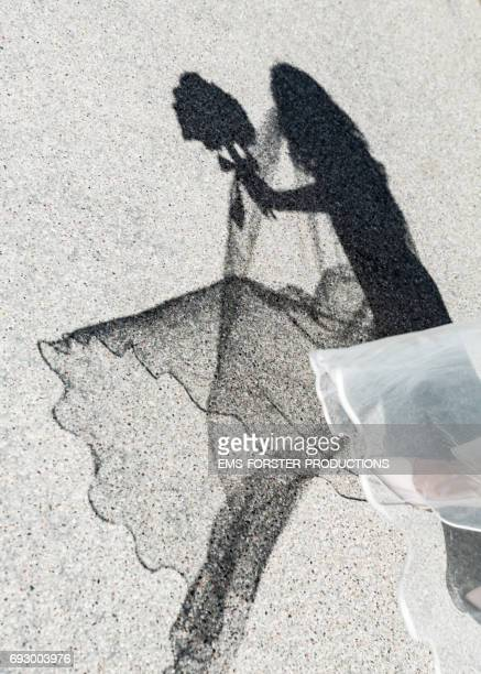 abstract shot of one foot of a bride wearing creme-coloured high heels pumps and her white wedding dress - dark shadow of the bride holding the bridal bouquet flowers in her hands appears on top of the street