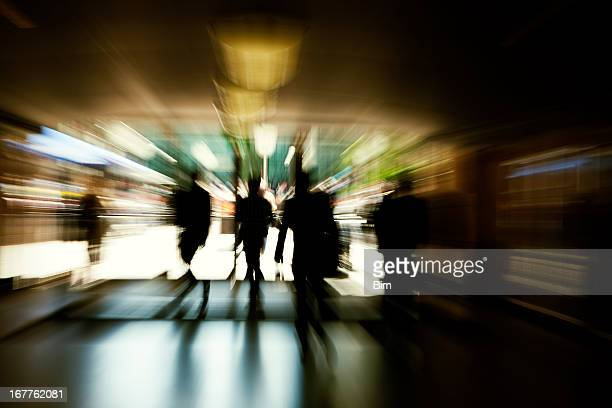 Abstract Silhouettes of Business Commuters Rushing Through Corridor