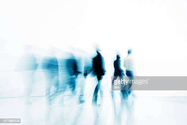 Abstract Silhouettes of Business People Walking Against White Background