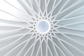 Abstract white space covered by a circular dome sustained by a radial structure with arches. Sunlight illuminates the wide vaulted space. A hole in the middle let the skylight come through. Balance, e