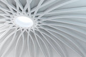 Abstract white space covered by a circular dome sustained by a radial structure with arches. Sunlight illuminates the wide vaulted space coming from an hole in the middle of the cupola. White material