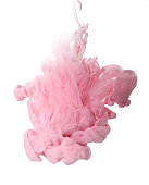 Abstraction of pink acrylic paint in water. Studio photography on a white background.