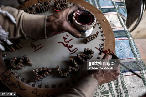 Abu Ali alBitar a 45yearold house painter who collected dozens of rocket debris and spent ammunition casings creates new artwork using spent...