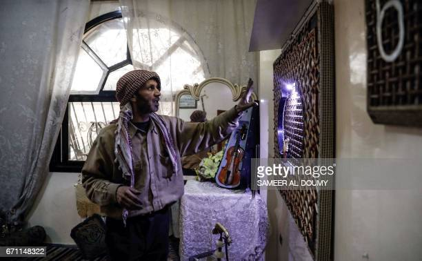 Abu Ali alBitar a 45yearold house painter who collected dozens of rocket debris and spent ammunition casings shows off some of his artwork in the...