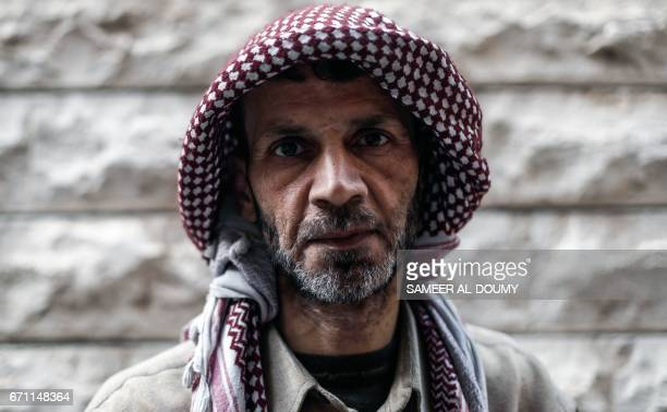 Abu Ali alBitar a 45yearold house painter who collected dozens of rocket debris and spent ammunition casings poses for a picture in the rebelheld...