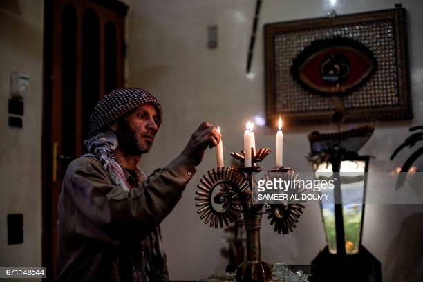 Abu Ali alBitar a 45yearold house painter who collected dozens of rocket debris and spent ammunition casings lights up candles on a candelabra made...