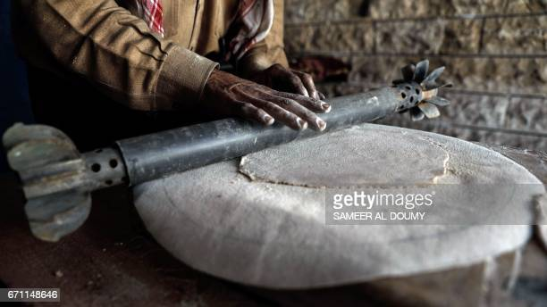 Abu Ali alBitar a 45yearold house painter who collected dozens of rocket debris and spent ammunition casings flattens bread dough using a leftover...