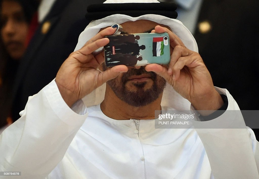 Abu Dhabi Crown Prince Sheikh Mohammed bin Zayed al-Nahyan takes a picture on a smart-phone during a visit to the Bomaby Stock Exchange (BSE) in Mumbai on February 12, 2016. The crown prince is on a three-day state visit to India. AFP PHOTO / PUNIT PARANJPE / AFP / PUNIT PARANJPE