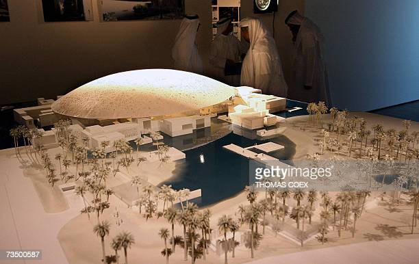Emirati men stand behind a scale model of the new Louvre Abu Dhabi museum 06 March 2007 France today signed a controversial deal worth one billion...