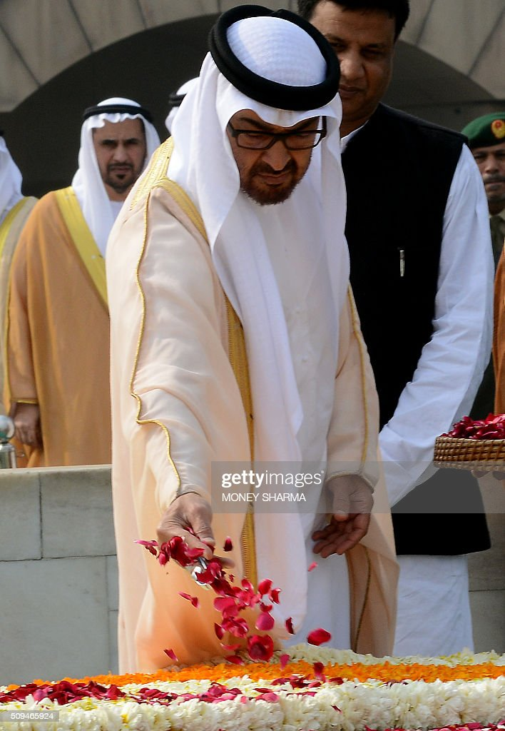 Abu Dhabi's Crown Prince Sheikh Mohammed bin Zayed al-Nahyan throws rose petals as he pays tribute at Raj Ghat, the memorial to the father of the Indian nation Mahatma Gandhi, in New Delhi on February 11, 2016. The crown prince is on three-day state visit to India until February 12. AFP PHOTO / Money SHARMA / AFP / MONEY SHARMA