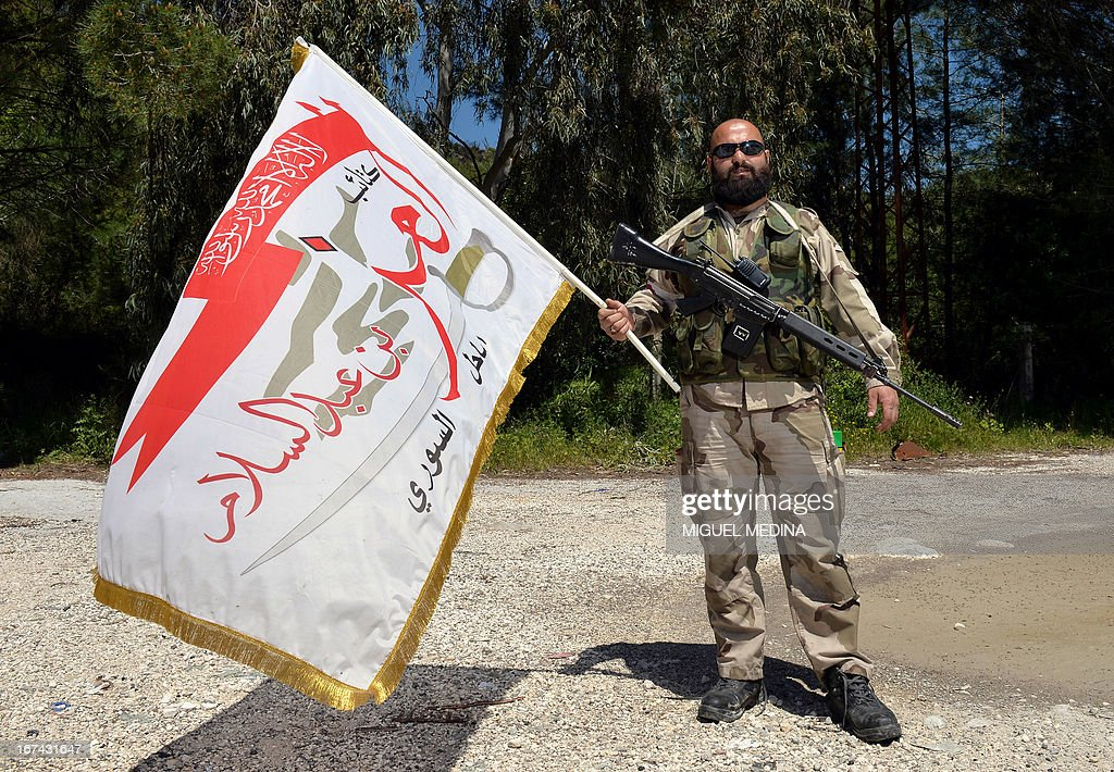 Abu Fahed a costume and props designer and member of the al-Ezz bin Abdul Salam brigade poses for a picture with the brigade flag during a training session at an undisclosed location near the al-Turkman mountains, in Syria's northern Latakia province, on April 25, 2013.