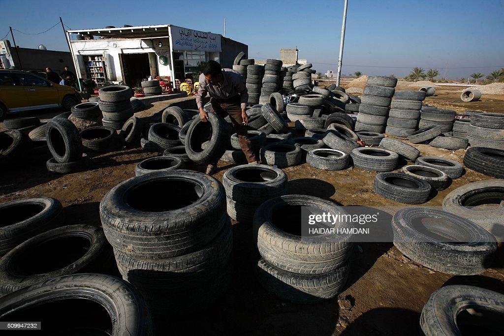 Abu Haidar arranges tires at his tire repair shop, where he transforms unused tires into furniture, in the Diwaniya village, east of the holy Iraqi city of Najaf, on February 13, 2016. / AFP / HAIDAR HAMDANI
