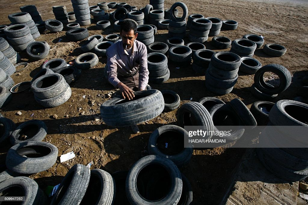 Abu Haidar arranges tires at his tire repair shop, where he transforms unused tires into furniture, in the Diwaniya village, east of the holy Iraqi city of Najaf, on February 13, 2016. / AFP / HAIDAR HAMDANI